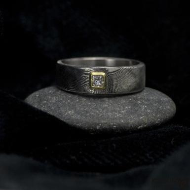 Snubní nebo zásnubní prsten damasteel - PRIMA + diamant princes 2,5 x 2,5 mm ve zlatě. Velikost 53,5 mm, šířka je 6,5 mm a do dlaně užší 5 mm, profil C. Struktura damasteel dřevo, lept 75%, zatmavený.